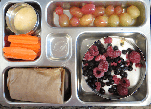 Calcium rich lunchbox:yogurt with frozen berries with granola (in a paper bag), carrots with miso dip, grapes