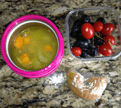 Soup-based lunchbox with a chicken soup, grapes and tomatoes and half a wholegrain bagel.