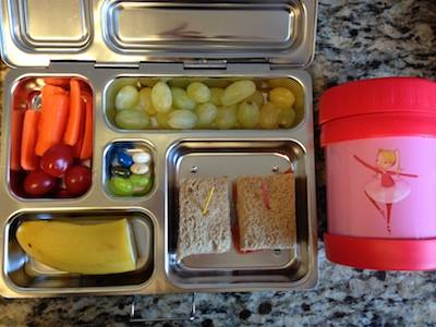 Soup-based lunchbox with lentil-kale soup, sandwich with smoked salmon, grapes, carrots and tomatoes, banana and jelly beans.